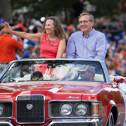 uf president kent fuchs and his wife riding in convertible in uf homecoming parade