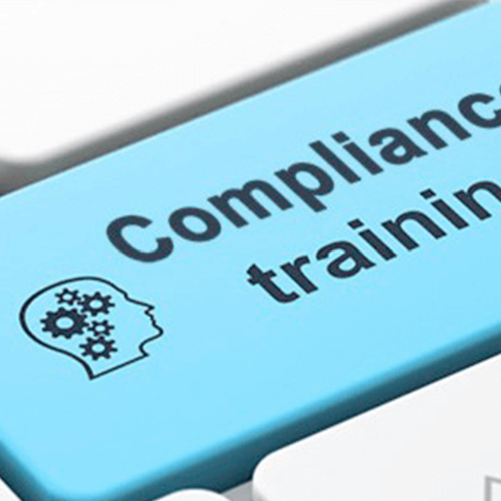 stock image of blue keyboard button that says compliance training