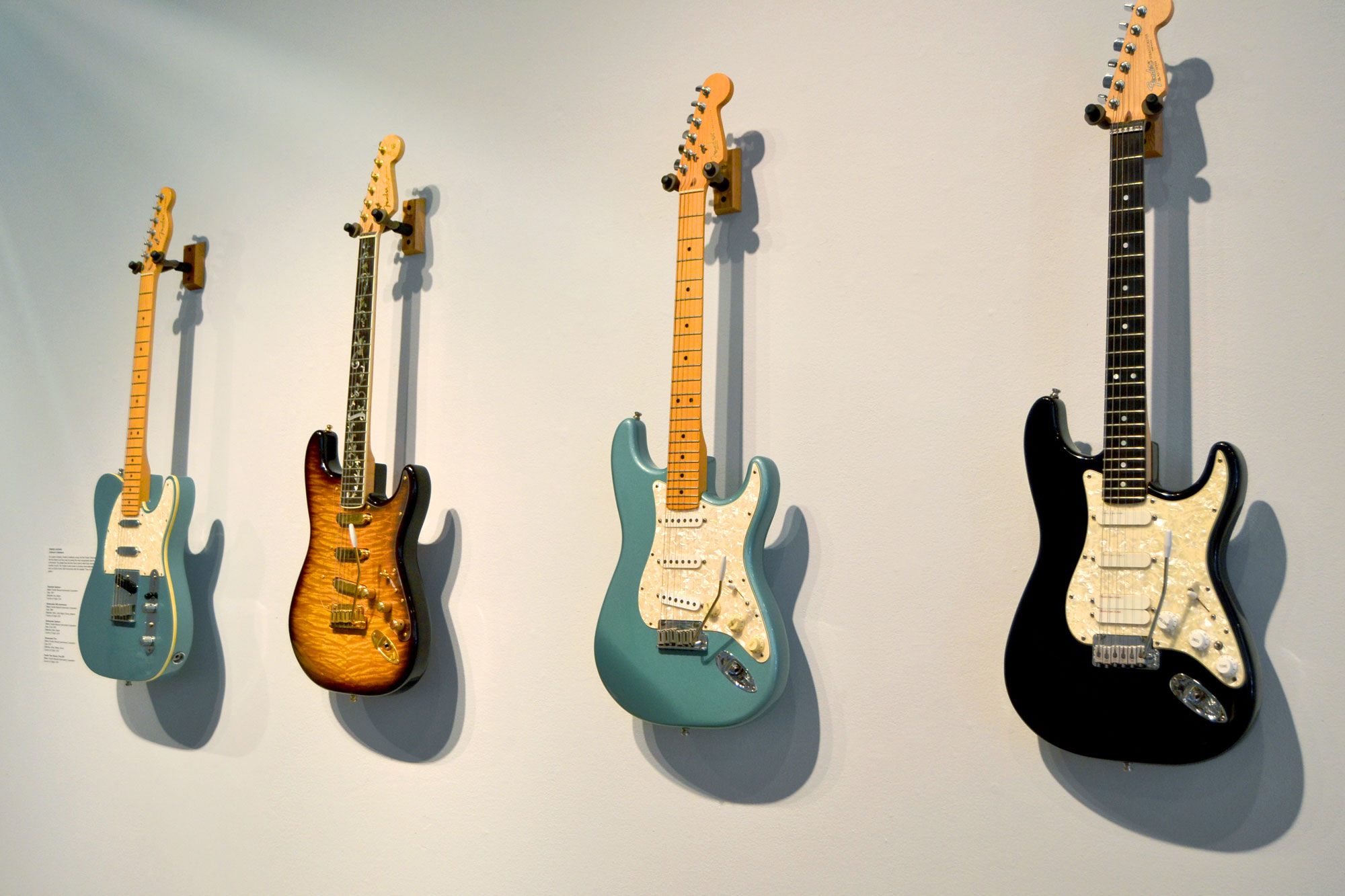 Image of guitars hanging on a gallery wall