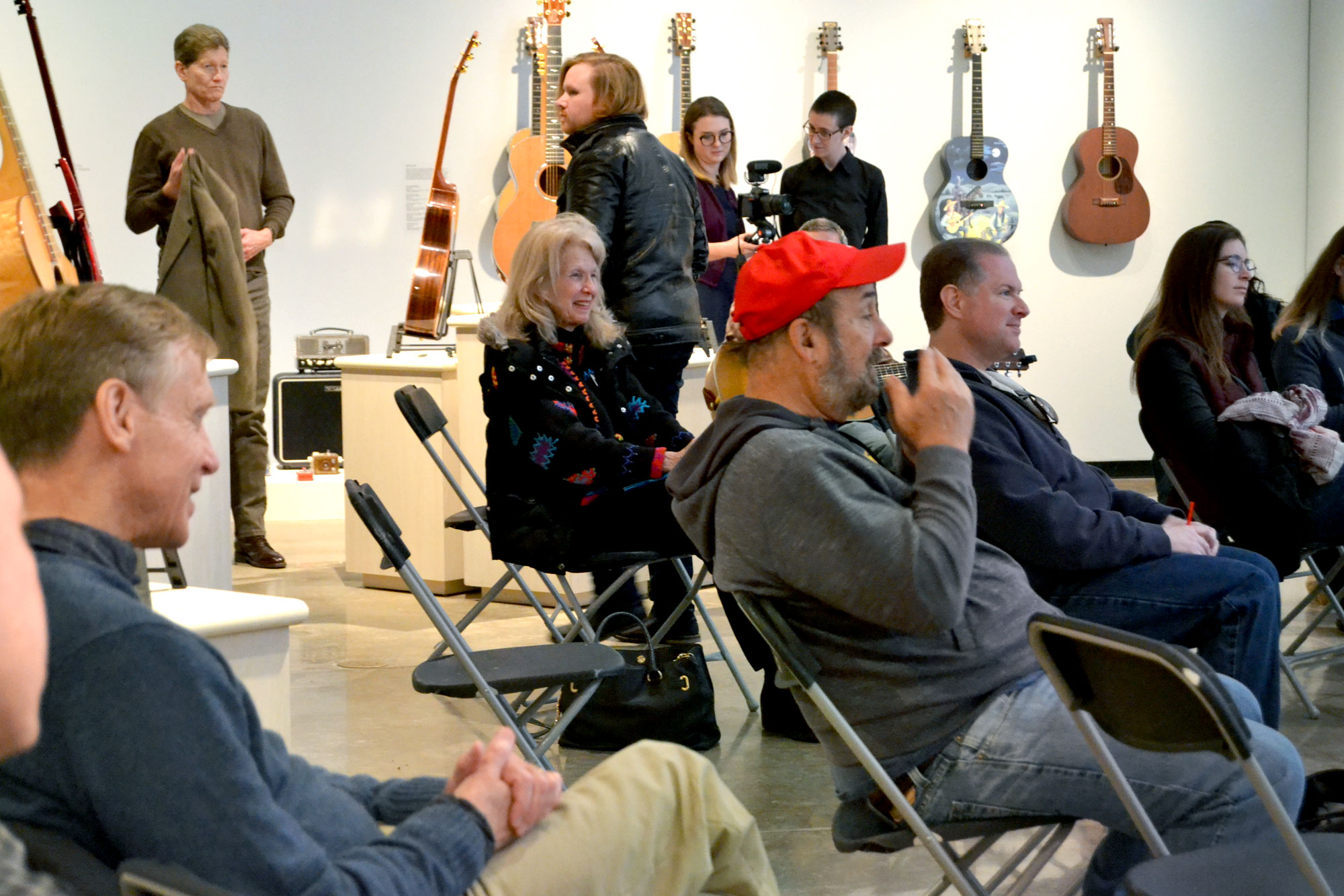 Image of an audience watching a bluegrass performance with a background of hanging guitars