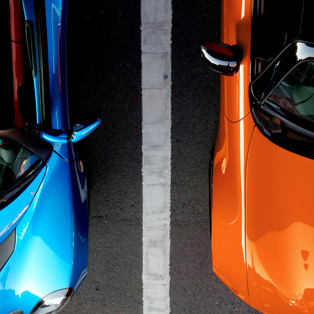 blue and orange cars in parking spaces
