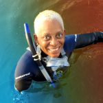 photo of diva in scuba gear, swimming with manatees, as part of crop summer event
