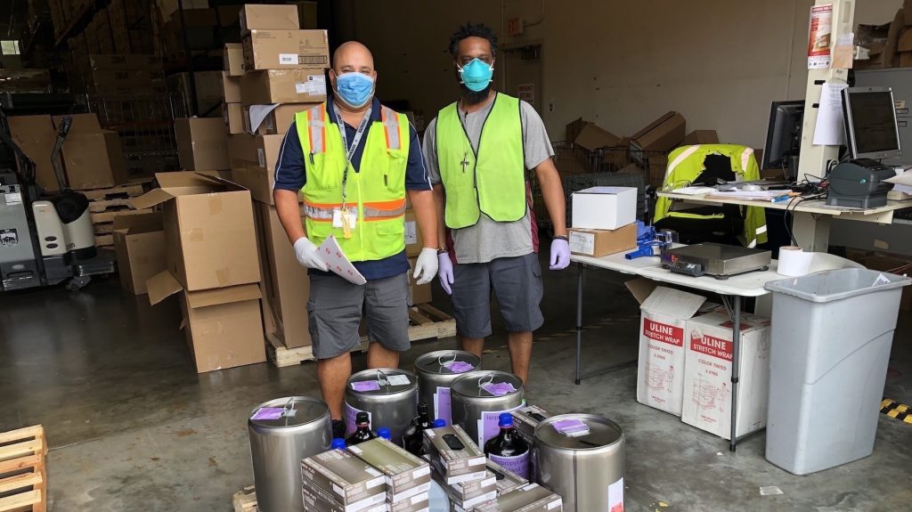 UF Health Warehouse workers receive hand sanitizer from UF Chemistry