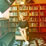 Woman sitting in chari in front of bookcase
