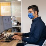 Faculty member wearing mask working at computer