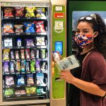 Person using vending machine to buy hand sanitizer and masks
