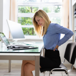 Woman sitting at desk with back pain