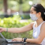Woman sitting outside wearing a mask next to a laptop