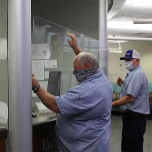man installing plexiglass